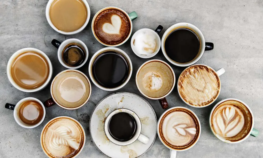 A variety of coffee cups all at different levels. They are sat on a grey workstation.