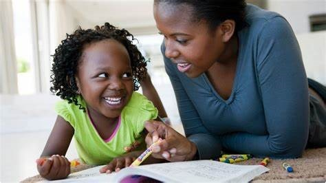 A lady looking at her child and helping with school work. The child is looking back and smiling at her mother