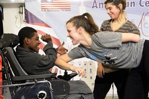 A young disabled wheelchair user bumping arms with a lady and smiling