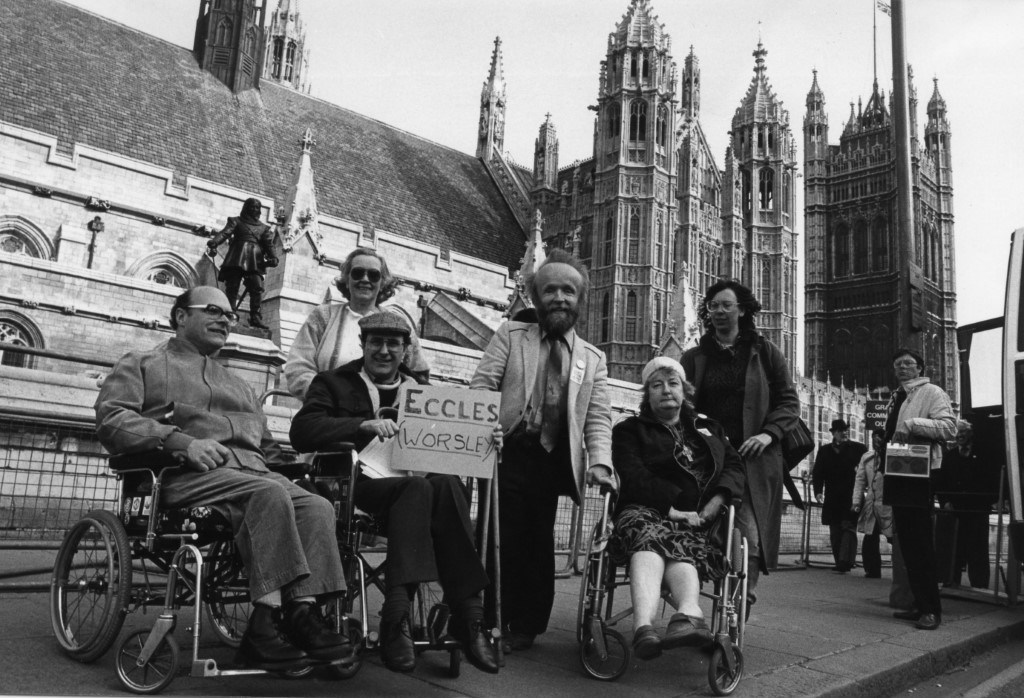 """A black and white picture of 6 GMCDP members in front of the houses of Parliment. One person, in the middle, is holding a placard saying """"Eccles (Worsley)"""""""