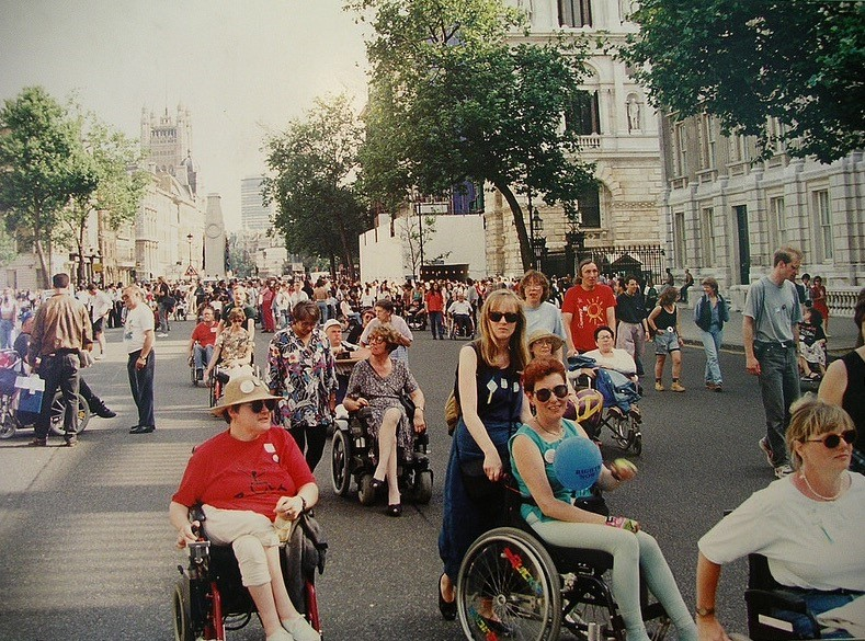 Disabled people and their supporters marching towards parliment in London. There is at least 100 people using a variety of different aids.